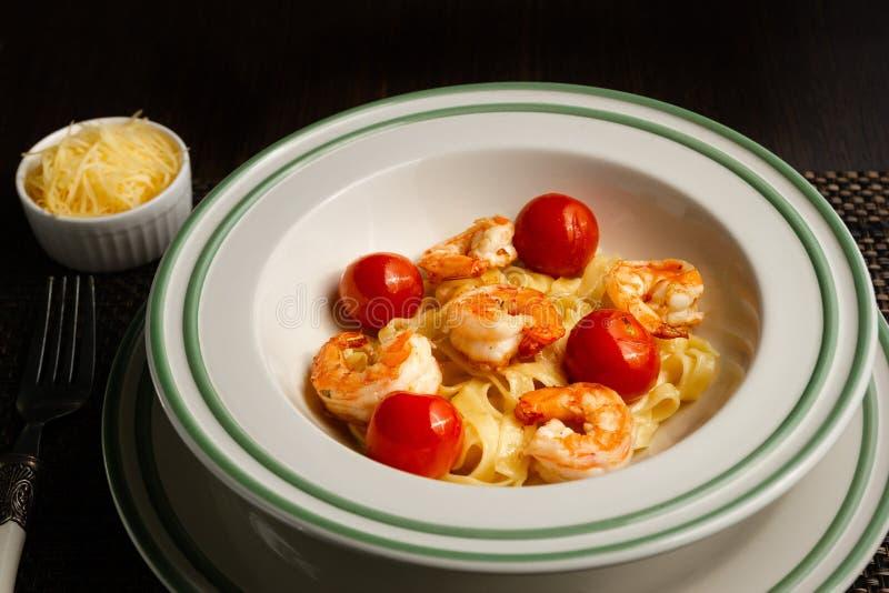Italiensk pastafettuccine i en krämig sås med räka på en platta, närbild arkivfoto