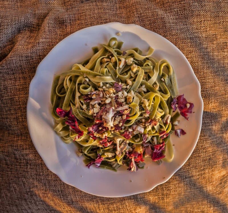 Italiensk pastamaträtt av den gröna tagliatellet med röd radicchio, waln arkivfoton
