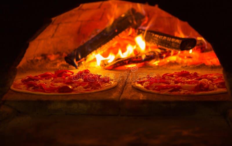 Italiensk pizza lagas mat i trä-avfyrad ugn royaltyfria foton