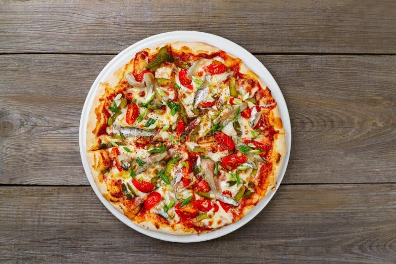 Italiensk pizza med ättiksgurkor och anchoviees, lekmanna- lägenhet arkivbilder