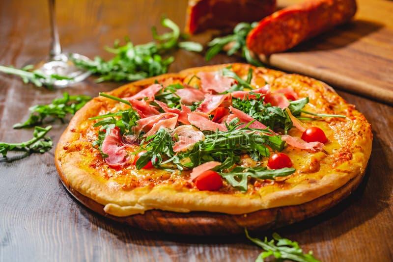Italiensk pizza med prosciuttoparma skinka, arugulasalladraket och körsbärsröda tomater på träbräde arkivfoto