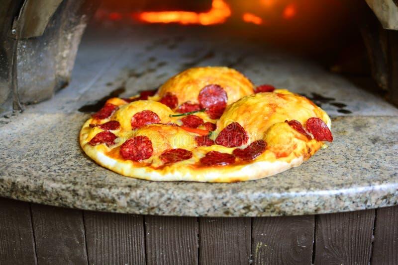 Italiensk pizza med salami från denavfyrade ugnen royaltyfri bild