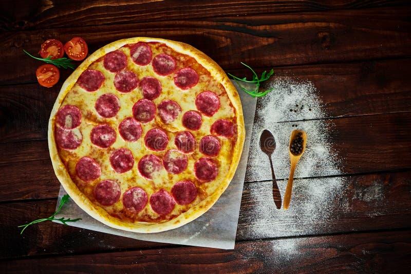 Italiensk pizza med saltar, ost och örter royaltyfria foton