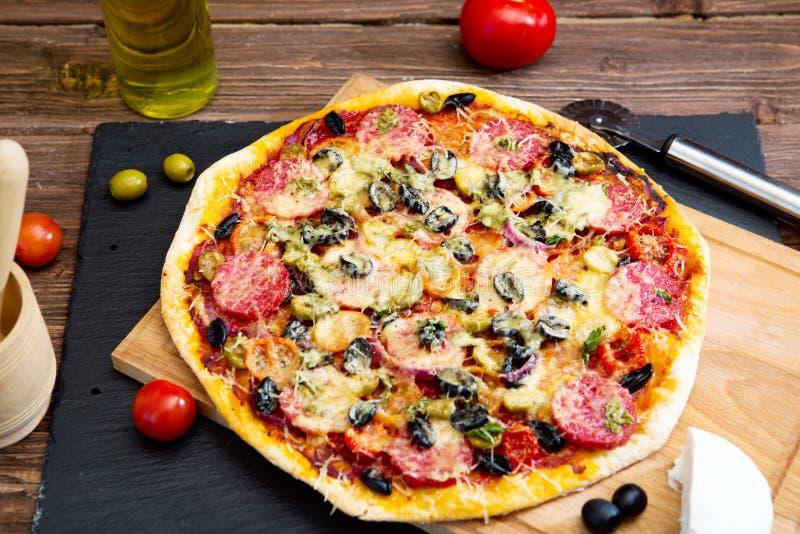 italiensk pizza Ny hemlagad pizza med peperoni-, ost- och tomatsås på lantligt utrymme för kopia för wirh för svartstenbakgrund royaltyfri fotografi