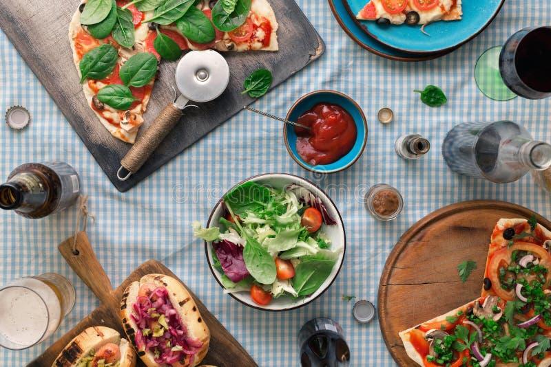 Italiensk pizza, varmkorv grillade, sallad, rött vin och lager arkivbilder