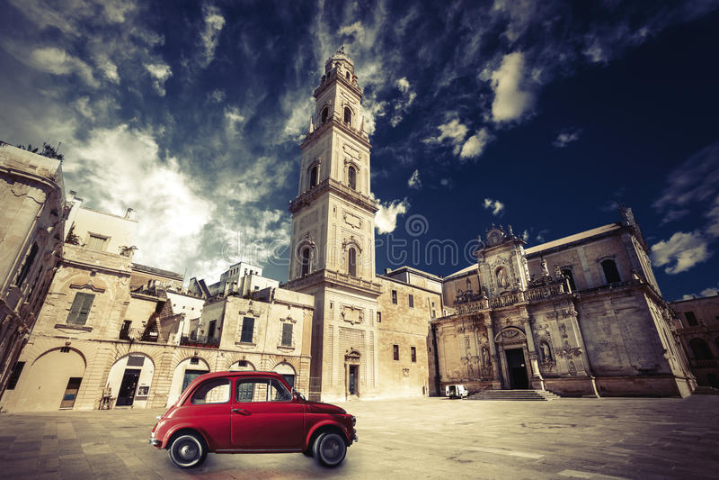 Italiensk plats för tappning, en gammal kyrka med ett klockatorn och gammal liten röd bil royaltyfria foton