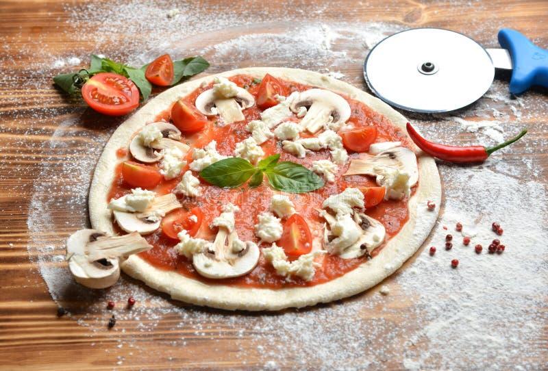 Italiensk process för pizzamatlagningförberedelse på den lantliga wood tabellen Pizzadeg och ingredienschampinjonchampignon royaltyfri bild