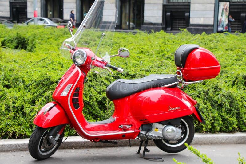 Italiensk röd sparkcykel för Vespa i gatan i Milano arkivbilder