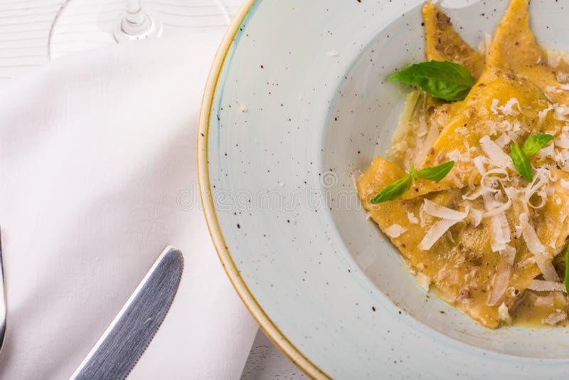 Italiensk raviolitortellini med basilika- och parmesanost på en vit platta royaltyfria foton