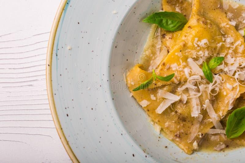 Italiensk raviolitortellini med basilika- och parmesanost på en vit platta royaltyfri bild