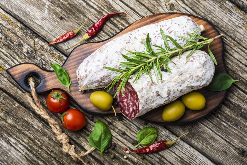 Italiensk salami med rosmarin, peppar, k?rsb?rsr?da tomater och oliv p? en tr?bakgrund Top besk?dar fotografering för bildbyråer