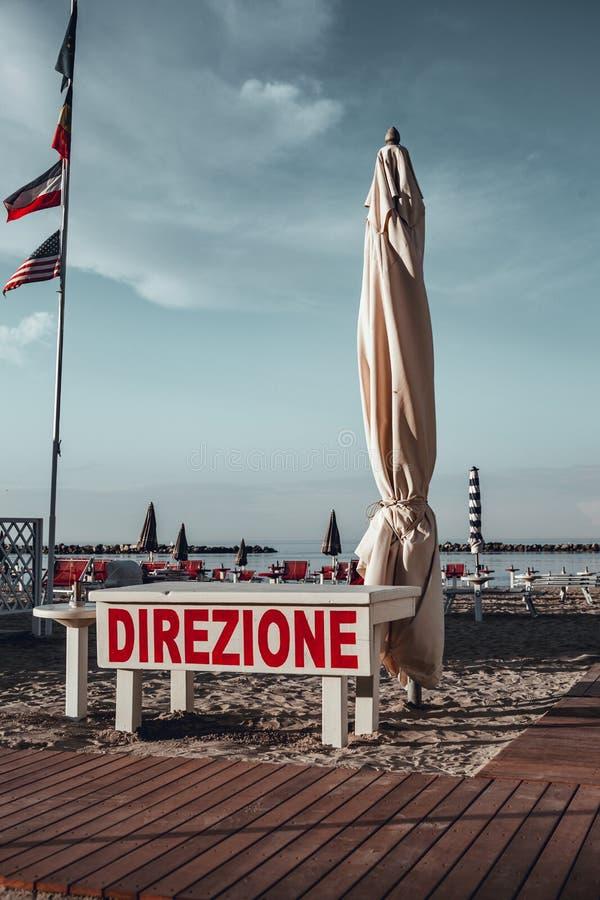 Italiensk sommar på Adriatiskt havet: tyipical italienska Riviera Romagnola strandklubbor med sunbeds och strandparaplyer med typ royaltyfri foto