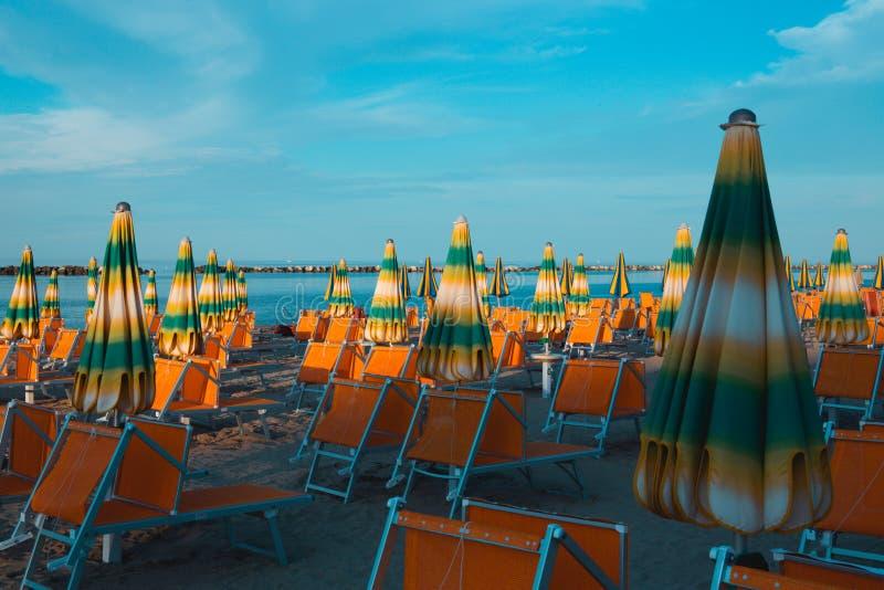 Italiensk sommar på Adriatiskt havet: tyipical italienska Riviera Romagnola strandklubbor med sunbeds och strandparaplyer med typ arkivfoto