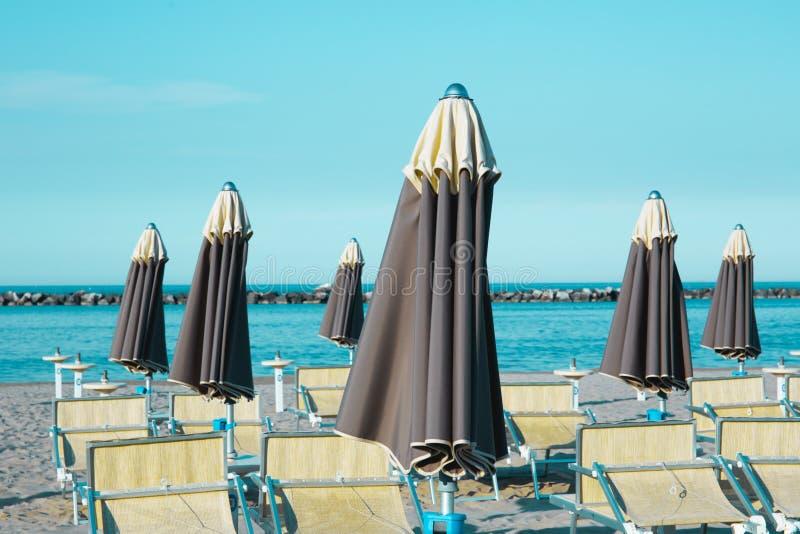 Italiensk sommar på Adriatiskt havet: tyipical italienska Riviera Romagnola strandklubbor med sunbeds och strandparaplyer med typ royaltyfria foton