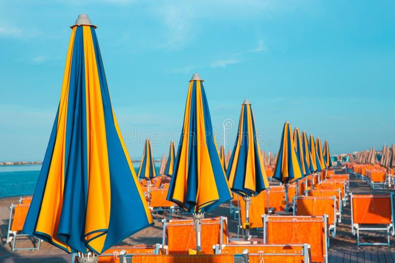 Italiensk sommar på Adriatiskt havet: tyipical italienska Riviera Romagnola strandklubbor med sunbeds och strandparaplyer med typ arkivfoton