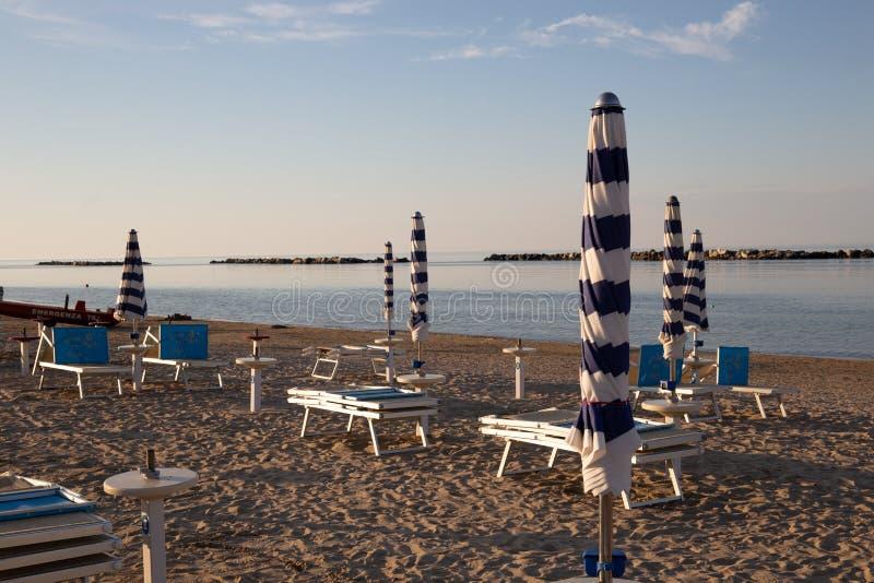 Italiensk sommar på Adriatiskt havet: tyipical italienska Riviera Romagnola strandklubbor med sunbeds och strandparaplyer med typ fotografering för bildbyråer