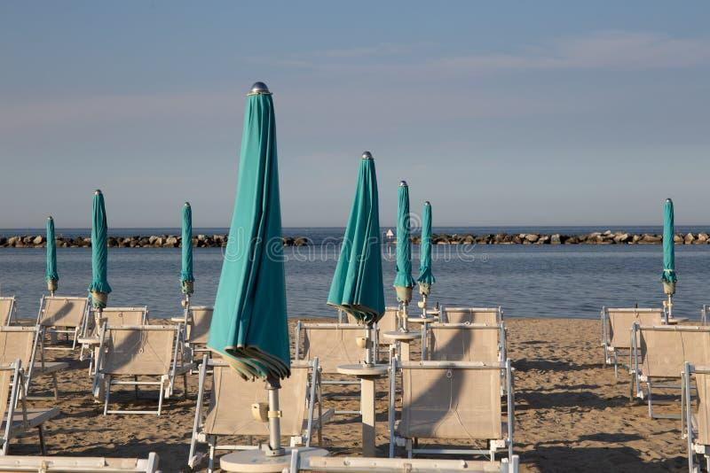 Italiensk sommar på Adriatiskt havet: tyipical italienska Riviera Romagnola strandklubbor med sunbeds och strandparaplyer med typ royaltyfri bild