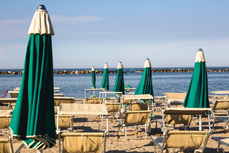 Italiensk sommar på Adriatiskt havet: tyipical italienska Riviera Romagnola strandklubbor med sunbeds och strandparaplyer med typ arkivbilder