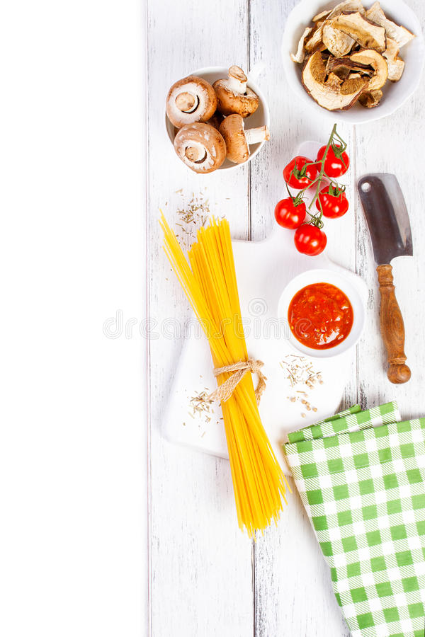 Italiensk spagetti, champignonen, torra champinjoner, tomatsås, nya körsbärsröda tomater och kryddor på en träbakgrund, pasta ing royaltyfria foton
