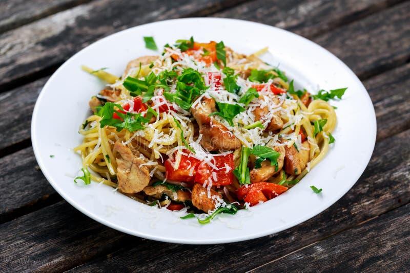 Italiensk spagetti för det fega bröstet med röd peppar, parmesanost och den lösa raket bor på den gamla trätabellen fotografering för bildbyråer