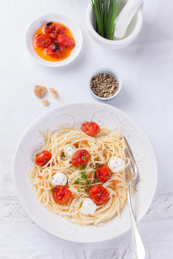 Italiensk spagettipasta med bakade körsbärsröd tomat-, mozzarella- och vårlökar royaltyfri bild