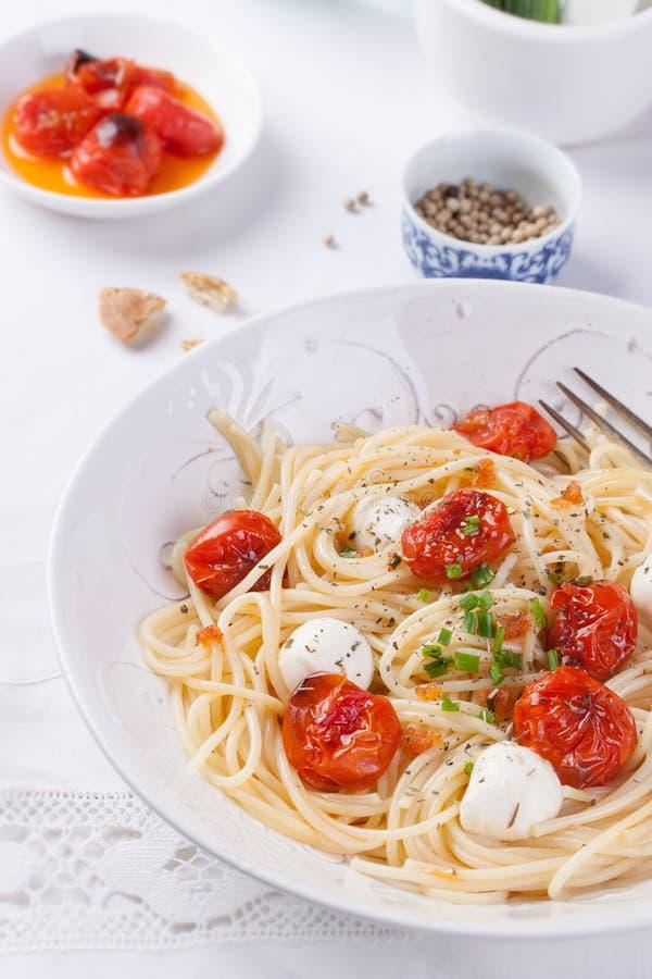 Italiensk spagettipasta med bakade körsbärsröd tomat-, mozzarella- och vårlökar fotografering för bildbyråer