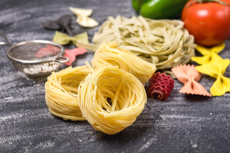 Italiensk traditionell mattagliatelle för rå pasta och Farfalle horisontalgrönsaker royaltyfri fotografi