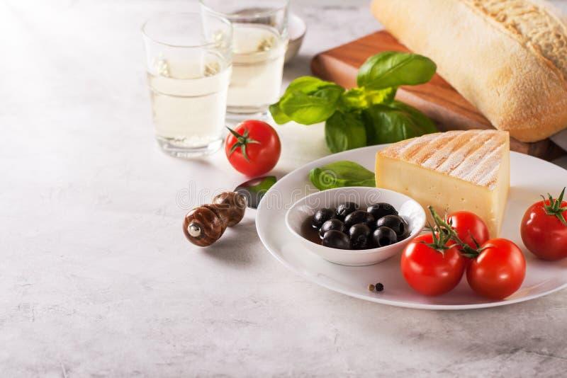 Italienska aptitretare, sikt från ovannämnt - panera ciabattaen, oliv, tomater, ost, peppar, ny basilika och vin arkivbilder