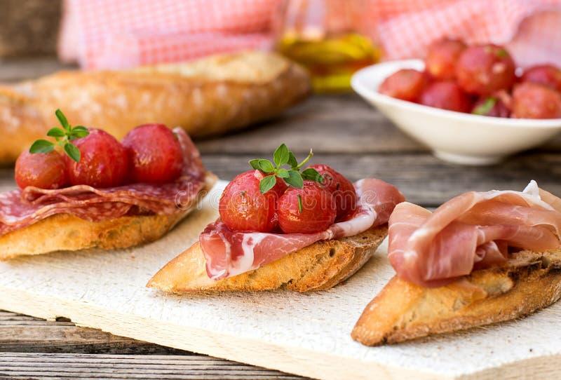 Italienska bruschettas med skinkaprosciuttoen, coppa, salami, körsbär t royaltyfri fotografi