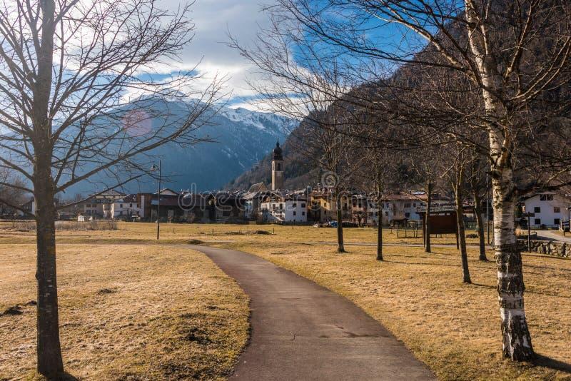 Italienska fjällängar, bana mellan träd som leder till den alpina byn arkivfoton