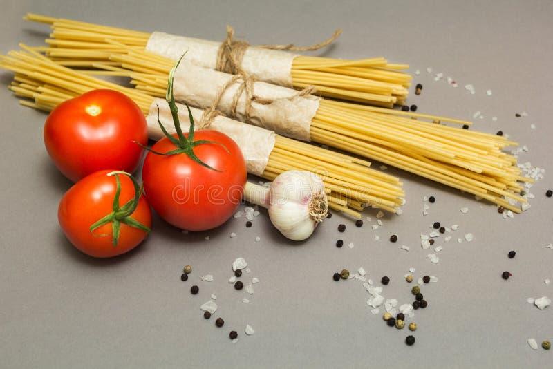 Italienska ingredienser av pasta- och grönsaktomater, pasta, vitlök, peppar, ost, kryddor på en grå bakgrund Begreppet av arkivfoto