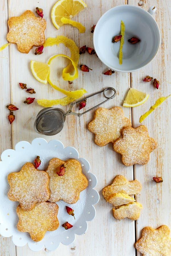 Italienska kakor, rosa färgknoppar och citron ovanför sikt royaltyfri fotografi