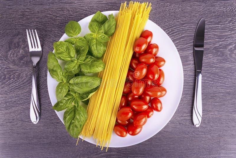 Italienska kokkonstingredienser på en vit platta royaltyfria bilder