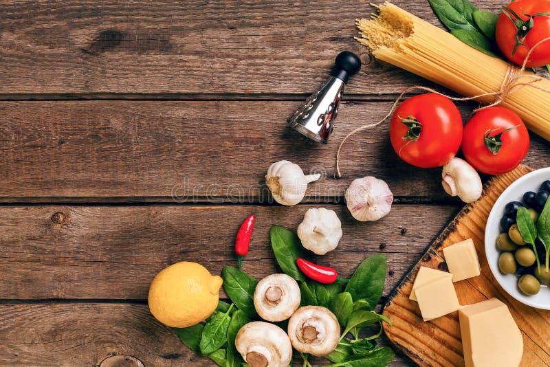 Italienska matingredienser för förberedelsepastan på träbakgrund royaltyfri fotografi