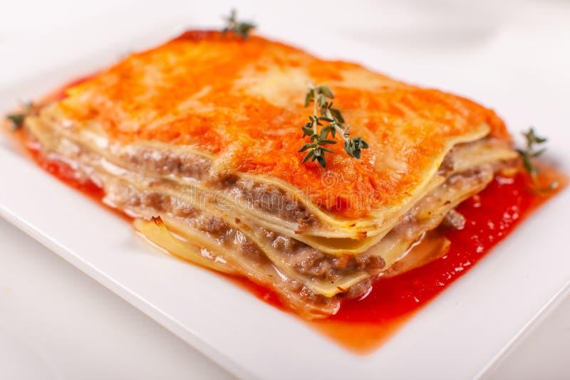 italienska matlagningmatingredienser Varma smakliga klassiska lasagner med bolognese sås på den vita plattan royaltyfri foto