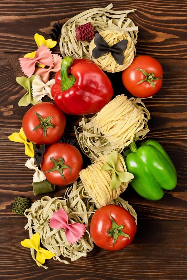 Italienska matpastaingredienser på trävariation för bakgrund för pasta för bästa sikt för tabell av pasta och grönsaker lägger fr arkivfoto