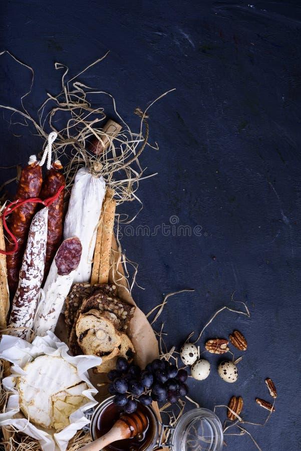 Italienska mellanmål med skinka, brödpinnar, druvor, ost arkivbilder
