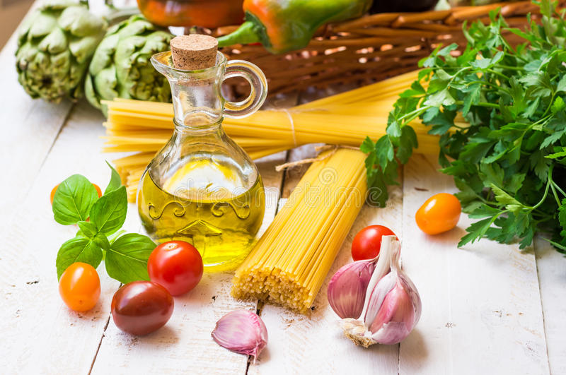 Italienska och medelhavs- kokkonstingredienser, spagetti, olivolja, vitlök, tomater, kronärtskockor, söt peppar i korg på kitch royaltyfria bilder