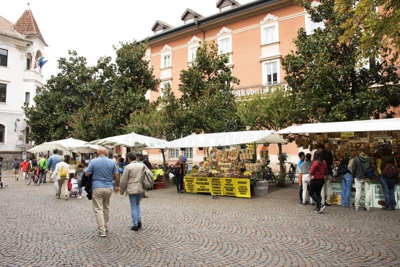 Italienskt folk som går lopp och shoppar på gatamarknaden för handgjord och organisk mat på den Meran staden arkivfoto