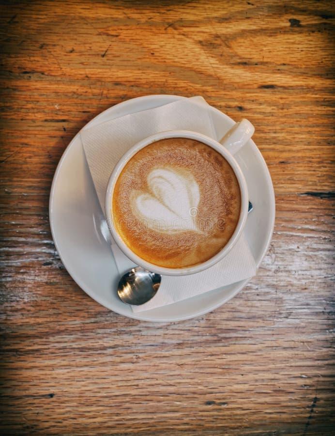 Italienskt varmt cappuccinokaffe med hjärta formade fradga på trätabellen royaltyfri foto