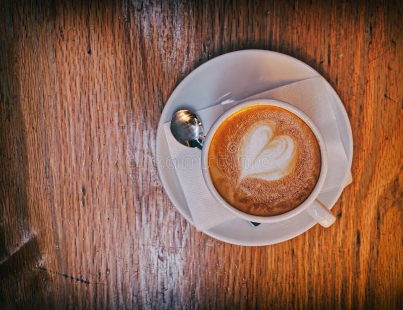 Italienskt varmt cappuccinokaffe med hjärta formade fradga på trätabellen royaltyfri bild