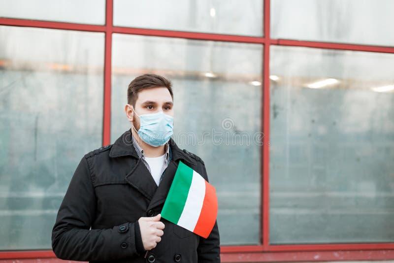 Italy coronavirus spreading outbreak. Man in medical mask, protective mask with Italian flag. Virus epidemic, Chinese coronavirusm. Outbreak influenza. Air stock photo