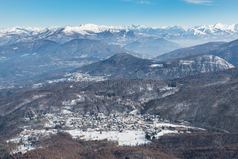 italy Den Campo deien regionala Fiori parkerar i förgrunden, med den Brinzio byn, i bakgrunden den alpina kedjan royaltyfri bild