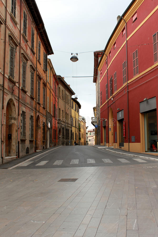 Italy. Emilia-Romagna. Cesena. Narrow street with red buildings on blue sky background. Vertical view. Italy. Emilia-Romagna. Cesena. Narrow street with red royalty free stock image