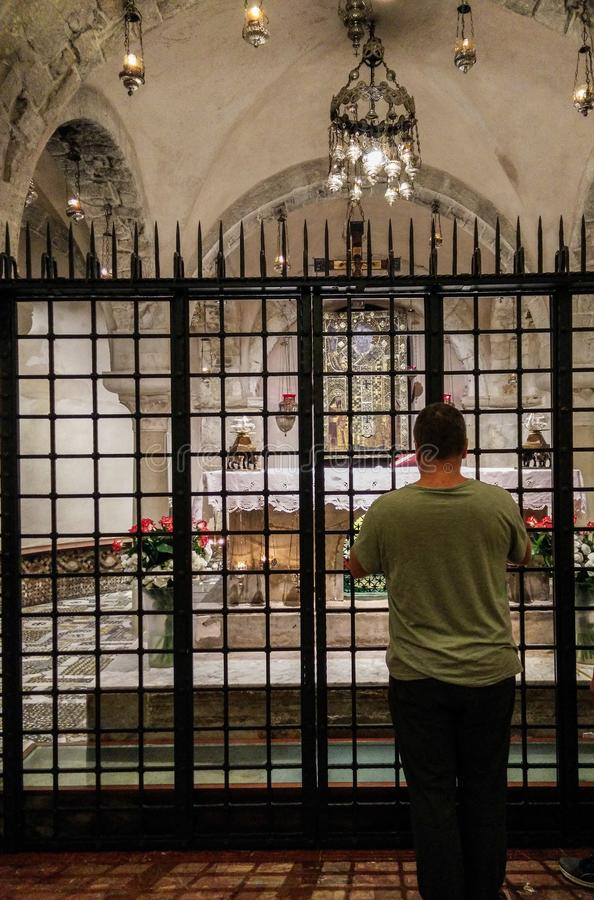 Italy. Faith and Religion. Bari. Basilica of San Nicola. A man prays in front of the chapel with the relics of the saint in cripta. The veneration for Saint stock photography
