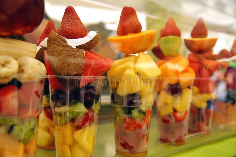 A plastic cup of fresh cut fruit. Delicious fruit salad arranged in plastic cups on the tourist market in verona royalty free stock photo