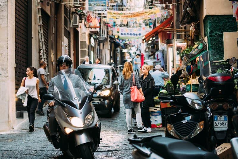italy naples Manridning på sparkcykeln på Vico Lungo Del Gelso Street Trafik på den berömda smala gatan royaltyfria foton