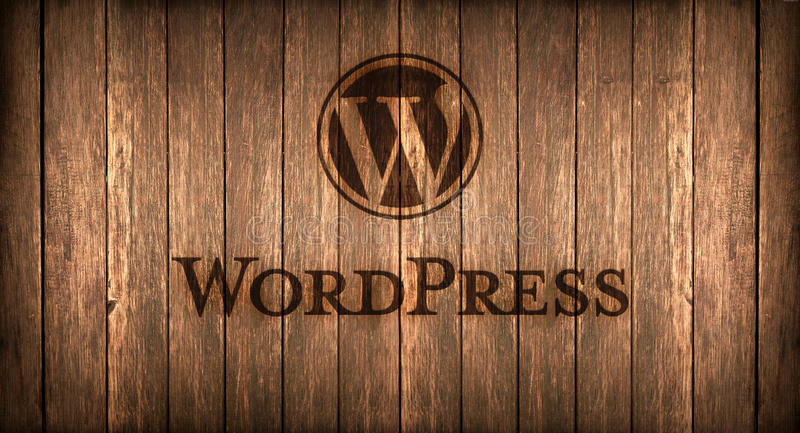 Italy, november 2016 - Wordpress logo printed on fire on a wood. Logo of a famous CMS printed on fire on a wooden board stock image