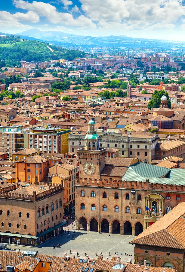 Italy Piazza Maggiore in Bologna old town. Tower of town hall with big clock and blue sky on background, antique buildings terracotta galleries royalty free stock images