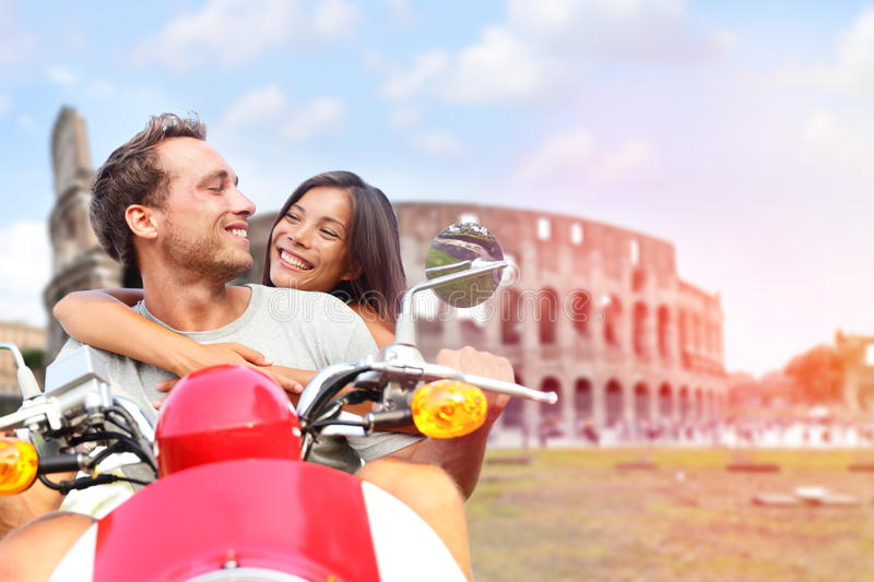 Italy Rome couple on scooter by Colosseum. Romantic happy lovers driving scooter on honeymoon having fun in front of Coliseum. Love and travel concept with royalty free stock photo